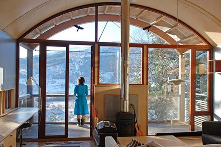 Photo of woman standing at window of DALE artists centre looking out at mountains