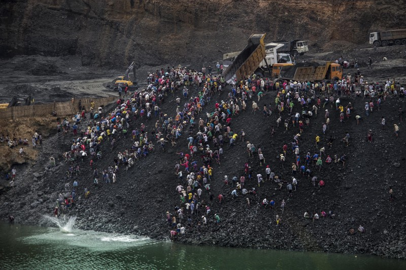 Small-scale miners search for stone as dump trucks from a government-licensed jade mining company dump waste in Hpakant, Kachin State, Myanmar, April 25, 2015. Jade mining a perilous job for small-scale miners especially when banks and slag heaps are de-stabilized by monsoon rain. A massive landslide in November 2015 at a government-licensed company waste-dumping site reportedly killed 114 people.