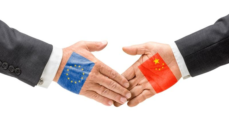 two hands joining in friendship, one overlain with an EU flag, the other with a Chinese flag
